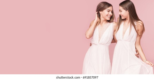 Gorgeous two caucasian twins models posing together on pink pastel background, smiling.