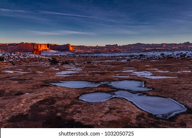 Gorgeous view of Frozen puddles on the sandstone floor of Arches National Park and glowing mountains at sunrise in Moab Utah USA.