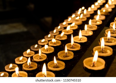 Gorgeous view of a full rack of lit prayer candles in a church.