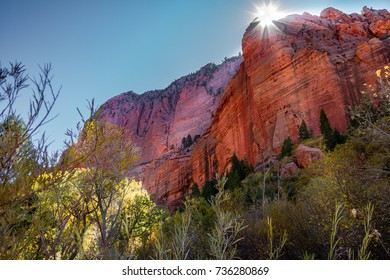 Gorgeous view of Kolob Canyon part of Zion National Park in Utah with a Sunburst illuminating the rock and sky.