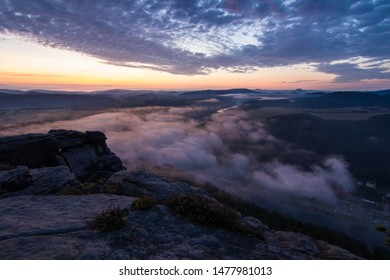 A gorgeous view from the rocks above a river during colorful sunrise. Cold from the river creating lovely fog adding to an amazing vista.
