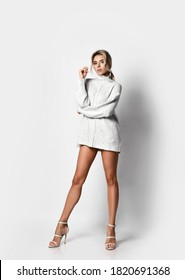 Gorgeous wealthy tall sexy blonde woman vamp in knitted sweater, naked long legs and high-heeled shoes stands with her arms crossed. Sexy female look and perfect body concept