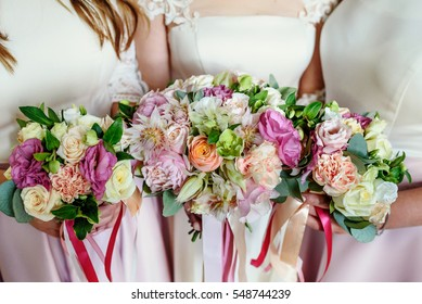 Gorgeous wedding bouquets made of pink and white flowers held by bride and bridesmaids