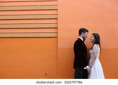 gorgeous wedding couple posing in front of orange wall