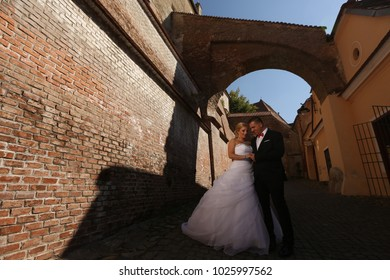 gorgeous wedding couple walking in the old city near brick wall