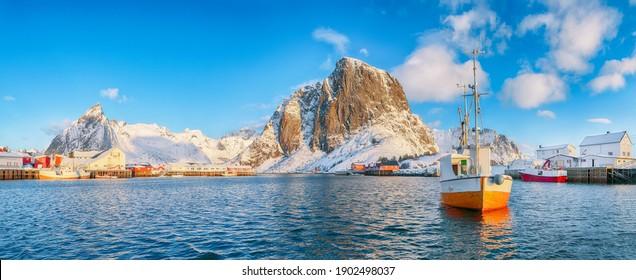 Gorgeous winter view on Hamnoy village with port and Festhaeltinden and Olstinden peaks on background.  Location: Hamnoy,  Moskenesoya , Lofoten; Norway, Europe