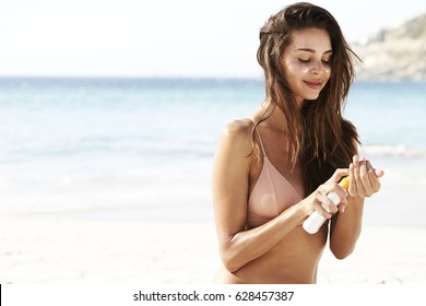 Gorgeous woman applying sunscreen at beach