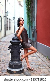 Gorgeous woman in beautiful dress is leaning with her back against old column in sexual and beautiful pose on the street of Old Riga, Latvia