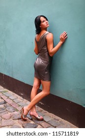 Gorgeous woman in beautiful dress is leaning to wall in sexual and beautiful pose on the street of Old Riga, Latvia