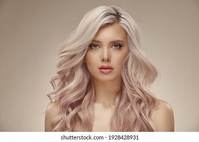 Belle femme avec de beaux cheveux roses ondulés sur fond beige