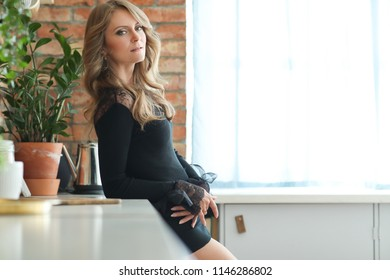 Gorgeous woman in black dress at the kitchen