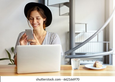 Gorgeous woman in black hat and blouse smiling while using cell phone chatting with her boyfriend sitting at table with laptop, glass of water and cake enjoying good day. Beauty and youth concept