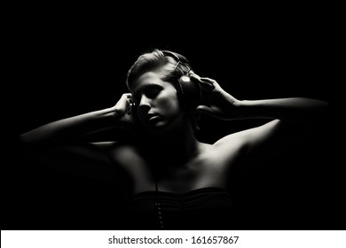gorgeous woman in black and white tense light listening to music