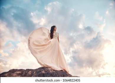 Gorgeous woman brunette in the mountains at sunset and blue sky with clouds. The woman looks into the distance in a long white dress developing in the wind. Summer sun sky nature vacation