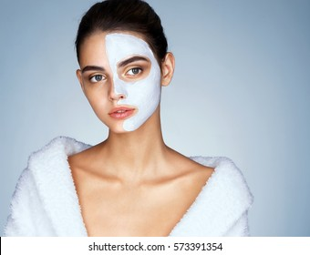 Gorgeous woman with cosmetic mask on her face. Photo of attractive brunette girl wearing white bathrobe. Wellness and Spa concept