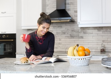Gorgeous woman drinking coffe and reading magazine in her kitchen