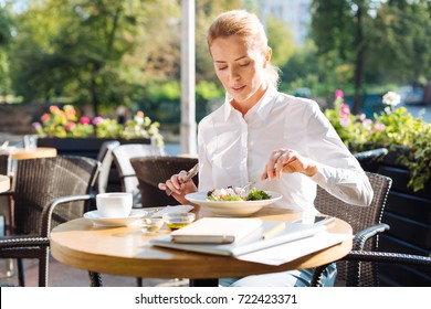 Gorgeous woman eating salad in cafe during lunchtime