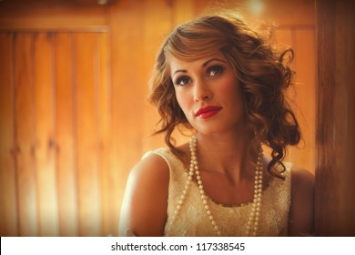 Gorgeous woman in flapper dress standing  in a train carriage
