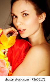 Gorgeous woman with flower and red silk looking at camera