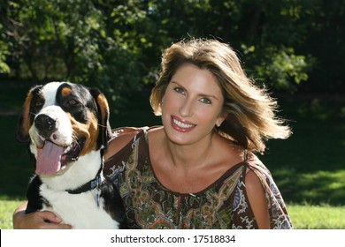 Gorgeous woman with her swiss mountain dog having fun outdoors in a park