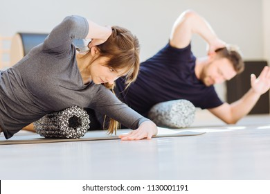 Gorgeous woman instructor performing back exercise on a foam roller at same time with handsome guy at pilates studio. Coach and patient doing fascia exercise on side surface of back.