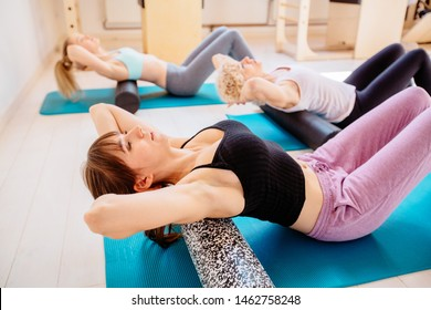 Gorgeous woman instructor performing exercise using a foam roller for a myofascial release massage with two females clients at pilates studio. Coach and patients doing fascial exercise of back.