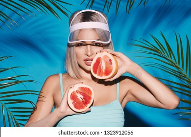 Gorgeous woman with nude make up posing at studio background with palms, holding fruit, close up portrait.