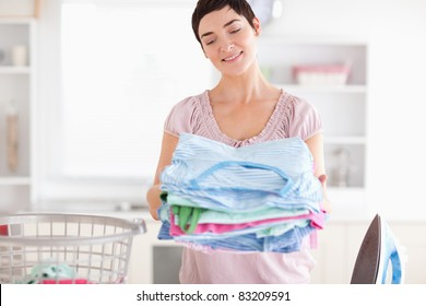 Gorgeous Woman with a pile of clothes in a utility room