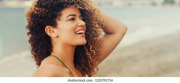 Gorgeous woman portrait smiling on the beach in Summer, letterbox