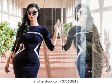 Gorgeous woman portrait wearing blue dress and sunglasses with reflection