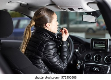 Gorgeous woman putting her lipstick on while sitting in her car. Woman doing some makeup in an automobile. Looking at her front mirror while putting makeup on.