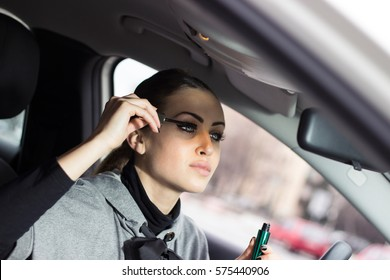 Gorgeous woman putting her mascara on while sitting in her car. Woman doing some makeup in an automobile. Looking at her front mirror while putting makeup on.