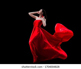 Gorgeous woman in red fluttered dress isolated on black background