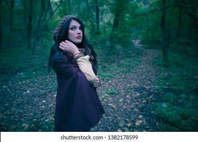 Gorgeous woman scared in autumn forest in the evening. Lonely woman in the woods. Girl running away from danger deep in dark forest. Scary autumn scene