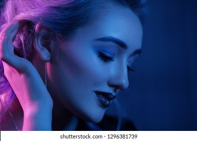 Gorgeous Woman With Sexy Makeup Looking Down. Side-View Portrait Of Seductive Girl's Face With Nightclub Makeup. Delicate Woman With Night Makeup And Rose Earing Gently Touches Her Blonde Hair.