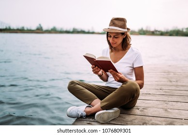 Gorgeous woman sitting on wooden pier and reading book.