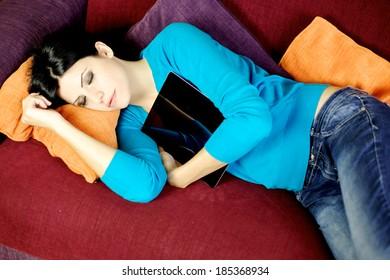 Gorgeous woman sleeping on sofa at home hugging