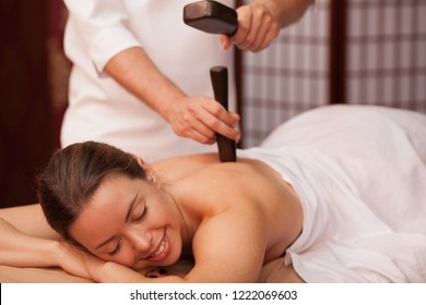 Gorgeous woman smiling with her eyes closed enjoying traditional thai hammer massage at spa center. Beautiful happy woman receiving tok sen massage by professional masseur. Travel, health concapt