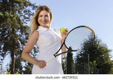 Gorgeous woman tennis player,  outdoor portrait while holding racket and ball
