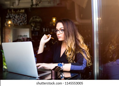 Gorgeous woman university student learning online via laptop computer, sitting in cozy coffee shop. Female in stylish glasses skilled freelance social media content writer working on pc notebook