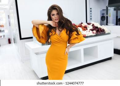 Gorgeous woman with volume brunette hairstyle, wearing evening cocktail yellow dress with sleeves and decollete. Party makeup on the face, big lips, white teeth. Standing near the vegetable counter.