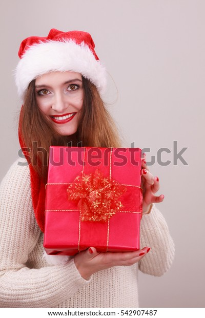 Gorgeous woman wearing santa claus hat holding red big gift box with ribbon. Xmas, happiness, winter and people concept.