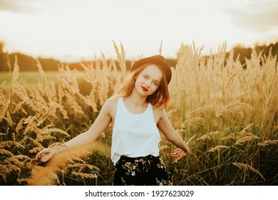 Gorgeous woman in a wheat field on a sunset background. A fashionable girl with long hair rejoices, laughs, enjoys life and summer, nature, happiness. Model in a hat in the forest.