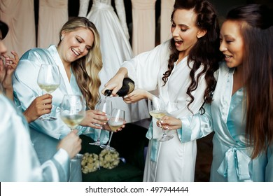 Gorgeous women in silk robes pour champagne in glasses