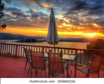 A Gorgeous Yellow and Orange Sunrise over a lake and red house deck with patio furniture and closed umbrella