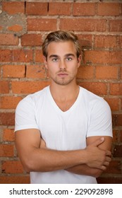 Gorgeous Young Blond Man in White Shirt Crossing Arms in Front on Bricks Wall Background. Looking at Camera.