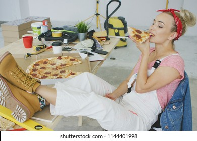 Gorgeous young blond woman in white overalls and work boots sitting relaxed with legs on desk eating piece of tasty pizza with instruments on background