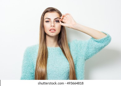 Gorgeous young blonde woman applying false eyelashes. Beautiful teenage girl with makeup, wearing light green soft sweater, posing on white background. Retouched, studio lighting.