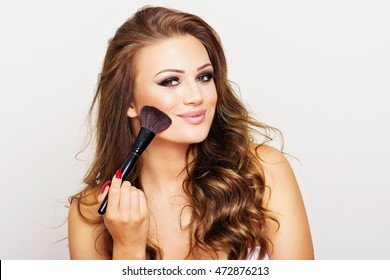 Gorgeous young blonde woman with long wavy hair smiling, posing, using makeup brush for applying blush. Teenage girl  doing her own makeup. Studio lighting, retouched.