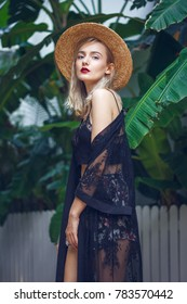 A gorgeous young blonde woman with straight cut hairstyle and with straw hat, green mysterious eyes and sexy red lips. She wears fashionable black lace clothing and golden necklaces.